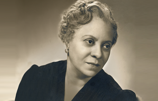 Florence Price in a black blouse with short, curly hair