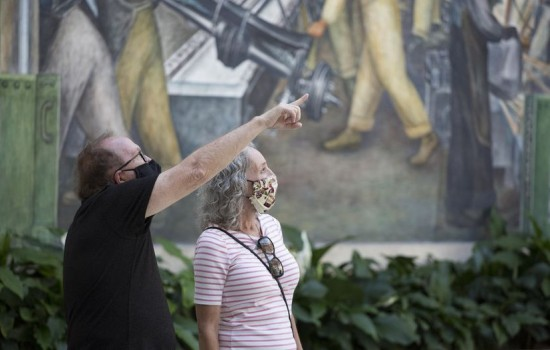Two patrons wearing masks in Rivera Court, viewing Diego Rivera's Detroit Industry Murals