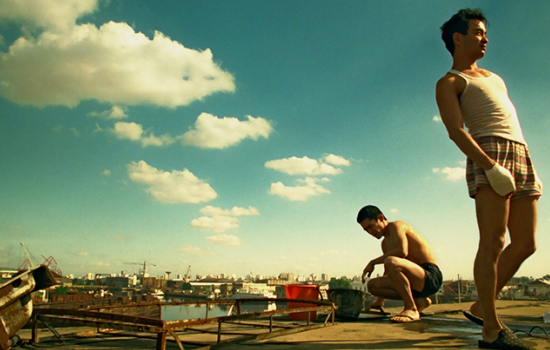 Two men in shorts stand atop a rooftop in a bustling city surrounded by a warm, blue sky. One of the men has his hand wrapped up in gauze.