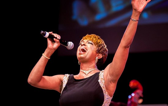 A photo of Joan Belgrave singing passionately