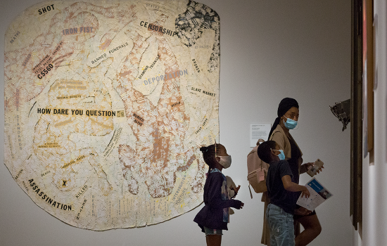 A mother and two young children wearing masks in the African American art galleries