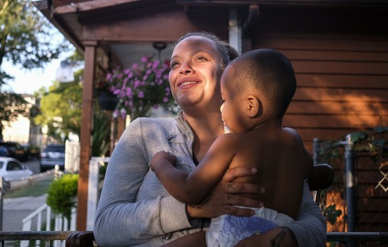 Ashley holds her son Nathaniel on the front porch of her house in Southwest Detroit.  August 17, 2017.