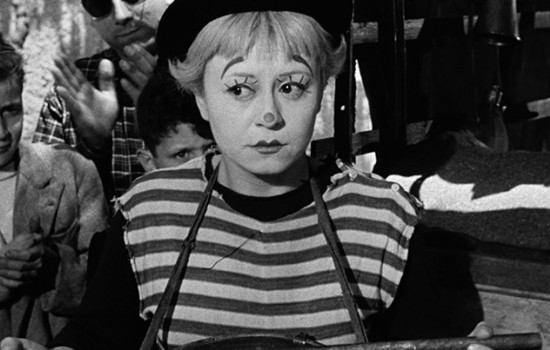 A black and white image of a woman in a striped shirt, black beret, and clown or mime makeup.
