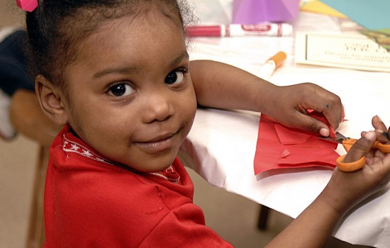 Young girl smiling while working on art in the art-making studio at the Detroit Institute of Aets