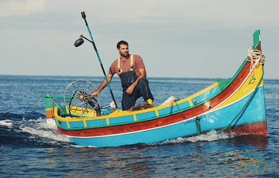 A man standing up in a small, brightly colored boat in open waters.