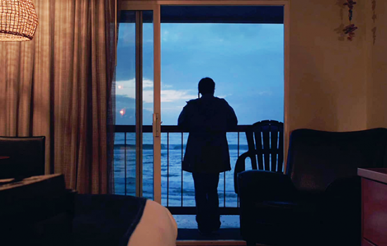An image of a shadowed figure standing on a balcony facing a body of water, photographed from behind a sliding glass door onto the balcony.