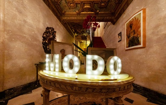 A grand marble room with the word MODO in bright lights