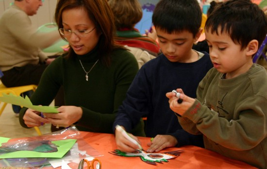 A mom and two sons crafting masks in the art-making studio