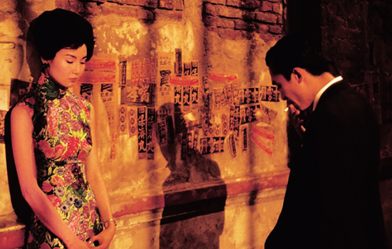 A woman stands against a wall with posters adhered to it as she talks to a man across from her on the sidewalk.