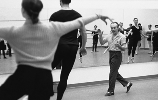 George Balanchine surrounded by dancing students in a mirrored dance studio.
