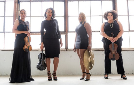 Four women, dressed in black, standing in a warehouse and holding their instruments