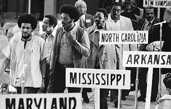 Black and white photograph of Black men, in 1970s clothing, walking down a row of signs featuring the names of U.S. states.