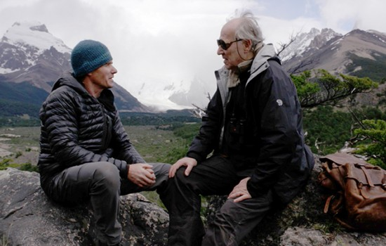 Two masculine presenting people sitting on boulders in front of a mountainside and having a conversation.