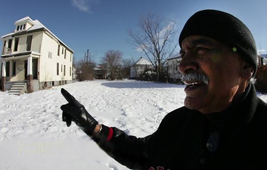 A man who appears to be taking a video of himself in front of a house on a city street with snow on the ground