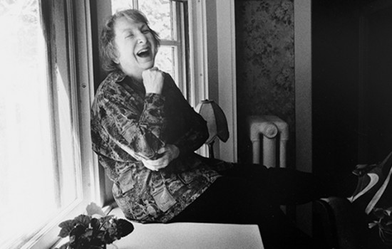 Pauline Kael in black and white, sitting and laughing by a window