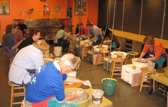 A group of artists using potter's wheels in the DIA's brightly colored art-studio