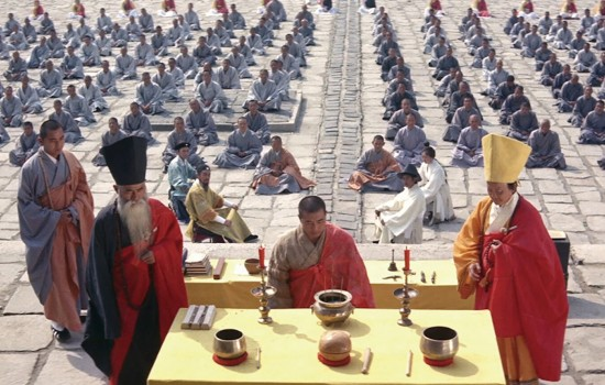 Three leaders in red stand at a table with candles while rows of people in blue sit behind them.