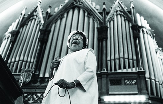 "A black and white photo of a woman singing in front of an organ from the film ""Say Amen, Somebody!"""