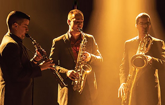 Three men playing wind instruments on a dark stage with a yellow light shining in the middle.