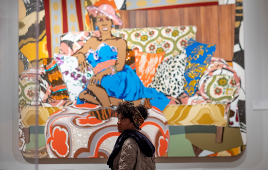 "A patron standing in front of Mickalene Thomas' ""Something You Can Feel"""