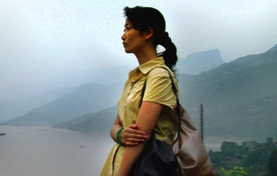A feminine presenting person wearing a yellow polo shirt, standing in front of a small lake and mountains