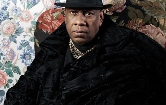 A photo of André Leon Talley in all black against a floral background