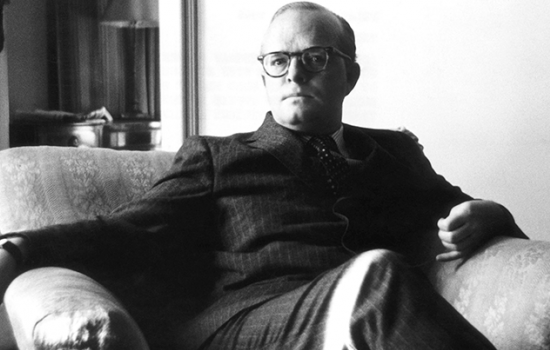 A black and white image of Truman Capote sitting in an armchair.