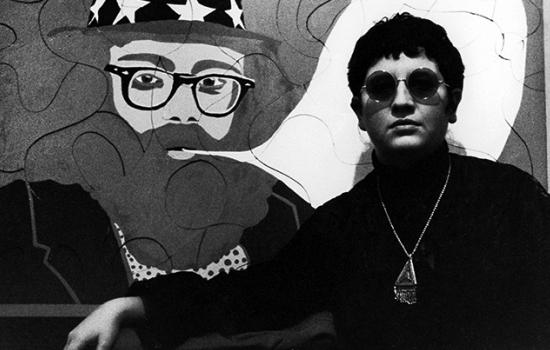 A person with short, curly hair wearing circular sunglasses, a black turtleneck and a large necklace sits in front of a painting of a man blowing smoke.