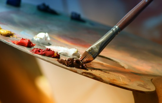 A paint brush bring brought to a painter's palette full of colors of paint.
