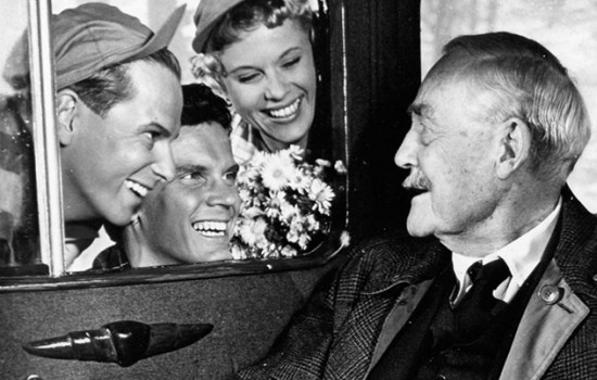 A still from the film Wild Strawberries by Ingmar Bergman featuring a man being given flowers through a car window.