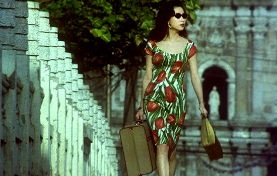 A woman in a rose-printed dress walks down a bridge holding a purse in one hand and small suitcase in the other.