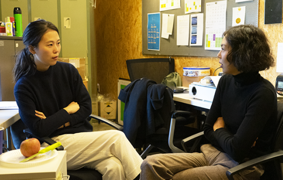 Two women, both wearing black turtleneck sweaters and khakis, sit opposite each other in an office setting.