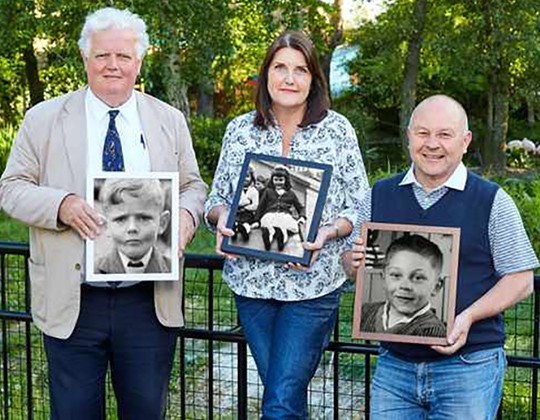 Three people from the film 63 Up, posing with photographs of themselves as children