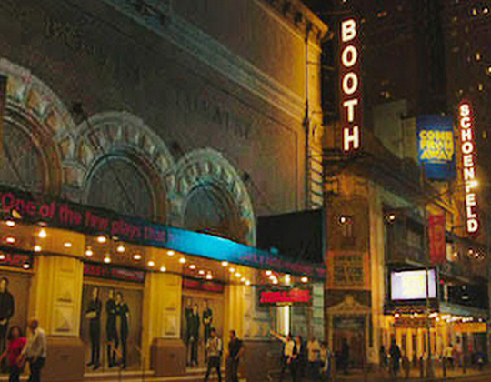 An image of Broadway with lighted signs in the evening.