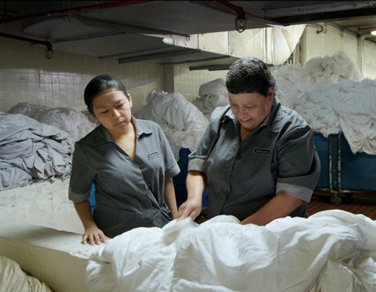 Two maids in a packed laundry room
