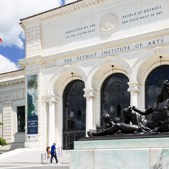 """The front facade of the Detroit Institute of Arts featuring banners for the exhibition """"Humble and Human: Impressionist Era Treasures, an exhibition in Honor of Ralph C. Wilson, Jr."""""""