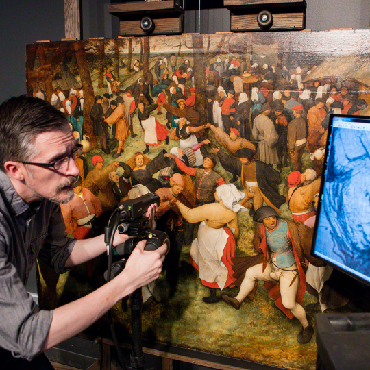 "DIA Conservator Aaron Steele using an imaging device on Bruegel's ""The Wedding Dance"""