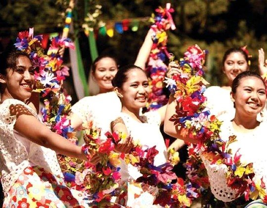 Filipino dancers in traditional dress holding floral garlands