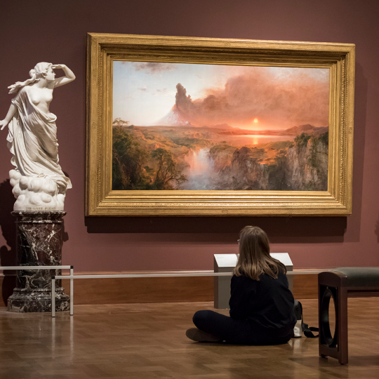 Young person sitting on the floor in front of Frederic Church's Cotopaxi