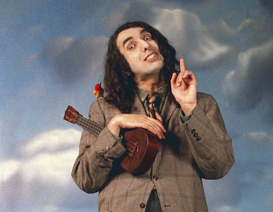 A man with long, curly hair poses in front of a cloudy sky background with a ukulele in hand and a small bird on his shoulder.