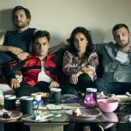 Five people with serious expressions sit on or around a small couch in this cramped photo. In front of them in the frame is a glass topped coffee table strewn with mugs, plates, drinking glasses, food, and other debris.