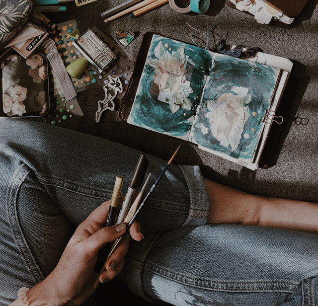 A person sitting crossed-legged on the floor with art supplies as they paint